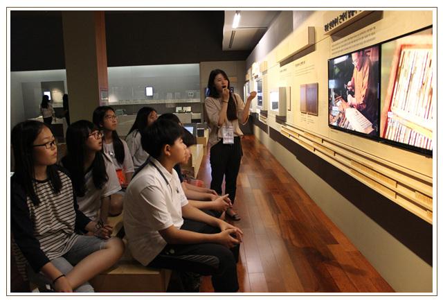 상설전시실의 영상에 대한 설명을 듣는 학생들
