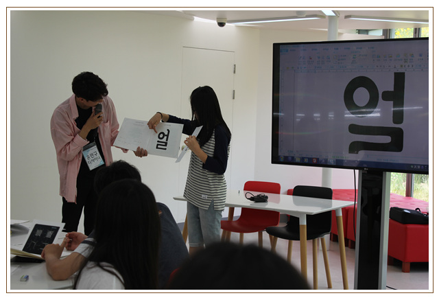 학생의 작품을 디지털 서체로 변환하여 직접 쓴 서체와 비교하며 이야기하는 선생님과 학생