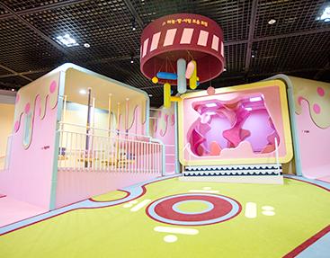 한글놀이터 모습. 천장에는 모빌이 매달려 있다. 짙은 붉은색 동그란 원형 통에는 '하늘·땅·사람 모음 모빌'이라고 적혀 있다. 파란색, 하늘색, 연두색, 분홍색 등 다양한 색상의 'ㅡ', 'ㅣ', '·' 모형이 매달려있다. 천지인을 활용한 디자인의 아래에는 넓은 공간이 있으며, 주변으로는 아이들이 체험할 수 있는 다양한 놀이 공간이 갖춰져 있다.