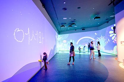 부 꿈꾸는 나의 방 전시 공간. 벽면에는 보랏빛 밤하늘 영상에 '어서와'라고 구름 글씨가 적혀 있다. 어린이들과 보호자들이 공간에서 자유롭게 전시를 관람하고 있다.