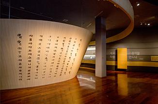 국립한글박물관 상설전시장의 일부 모습. 벽에 '새로 스물여덟 자를 만드니'가 적혀있다. 어두운 전시장에 훈민정음 내용이 적힌 커다란 기둥 구조물이 놓여있다.