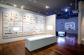 국립한글박물관 상설전시장의 일부 모습. 하얀 벽면에 다양한 한글 타이포그래피들이 벽면 가득 전시되어 있다. 벽면 앞에는 하얀색 진열장이 놓여있다. 그 옆 벽면에는 '사랑'이라고 적힌 한글 타이포그래피가 하얀 조명으로 제작돼 빛나고 있다. 아래에는 오래되어 보이는 작은 컴퓨터가 유리 상자 안에 전시되어 있다.