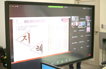 촬영장에 세워져 있는 대형 모니터 화면. 실시간으로 송출되는 교육 화면을 보여주고 있다. '지혜'라는 단어를 이용해 세모꼴의 궁체에 대해서 설명하는 영상이 송출되고 있다. 영상 옆엔 줌 수업에 참여한 외국인 학생들의 모습이 보인다.