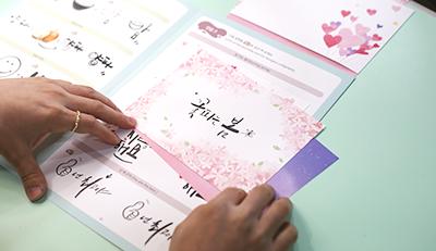 캘리그래피 수업을 진행 중인 모습. 책상 위 강사가 적은 '꽃 피는 봄'이 적힌 엽서가 놓여있다. 테두리에 분홍색 꽃이 둘려 있다.