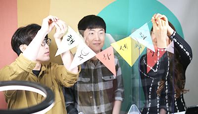 캘리그래피 수업을 진행 중인 모습. 세 강사가 나란히 앉아있다. 왼쪽과 오른쪽에 앉은 강사가 '행복하세요'가 적힌 벽걸이 장식의 끝을 잡고 있다. '행', '복', '하', '세', '요' 각 글자는 알록달록한 삼각형에 한 글자씩 쓰여 있다.