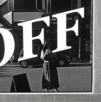 정지현 디자이너가 직접 찍은 자신의 모습. 커다랗게 OFF라고 적힌 거울 앞에선 정지현 디자이너가 핸드폰으로 자신의 모습을 찍고 있다. 뒤로는 건물과 도로, 자동차 등이 보인다. 사진은 흑백으로 표현됐다.
