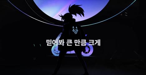 케이디에이의 '더 배디스트' 뮤직비디오 속 한 장면. 어두운 배경과 함께 게임 '리그오브레전드'의 캐릭터 아칼리의 뒷모습이 어둡게 표현되어 있고, 그 위에 하얀 글씨로 '믿어봐 큰 만큼 크게'가 적혀있다.